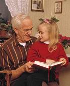 Äldre man och flicka läser bok