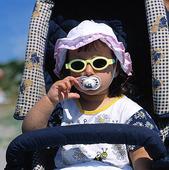 Barn med solglasögon och napp