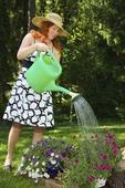 Kvinna vattnar växter