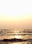 Solnedgång över disigt hav