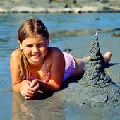 Flicka bygger sandslott
