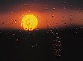 Solen bakom regnigt fönster