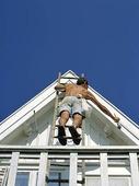 Man målarpå taknock