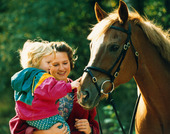 Kvinna och barn vid häst
