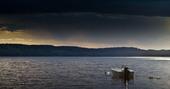 Mörka moln vid förtöjd motorbåt