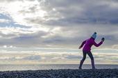 Flicka kastar stenar i havet