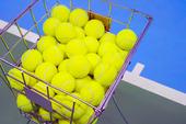 Tennisbollar i korg
