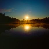 Soluppgång vid insjö