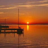 Segelbåt vid brygga i Solnedgång