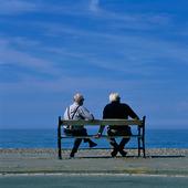 Två män på bänk vid havet