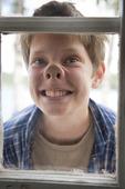 Pojke utanför fönsterruta