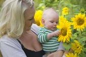 Mamma med barn tittar på solros