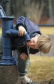 Pojke som dricker ur vattenpump