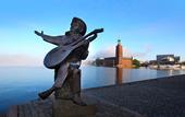 Evert Taube staty med Stockholms stadshus i bakgrunden