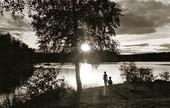 Barn vid insjö i solnedgång
