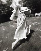 Flicka som spriger på gräsmatta
