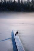 Barn och vuxen på snöig brygga