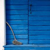 Sopborste vid blå dörr