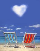 Två solstolar på stranden med hjärtformat moln på himle