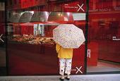 Människa med paraply vid skyltfönster