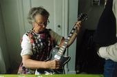 Äldre kvinna med elgitarr