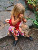 Flicka leker med docka