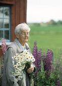 Äldre kvinna med blommor