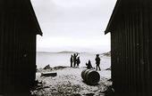 Barn leker vid sjöbodar