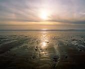 Solnedgång över sandstrand