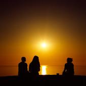 Människor i solnedgång vid havet