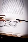 Gammal bok med en penna och gamla glasögon