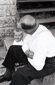 Äldre man pratar med pojke