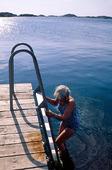 Kvinna badar från brygga, Bohuslän