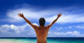 Man står tittar på havet med armarna utsträckta