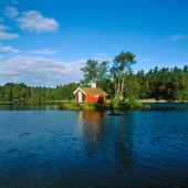 Röd stuga på en ö i en sjö