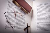 Läsglasögon och en penna om på en bok