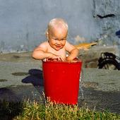 Barn som badar i hink med vatten