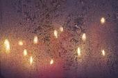 Stearinljus bakom frostigt fönster