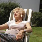 Äldre kvinna i trädgårdstol