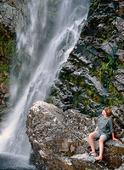 Flicka vid vattenfall