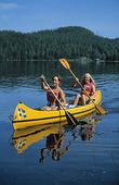 Flickor paddlar kanot