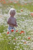 Liten pojke på blomsteräng