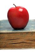 Rött äpple på gammal bok